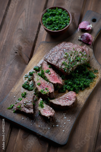 Chopping board with medium rare beef steak and chimichurri Poster