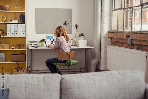 Photo studentin sitzt zuhause am schreibtisch und arbeitet am laptop