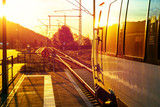Modern passenger train standing at countryside platform with beautiful landscape at sunset.