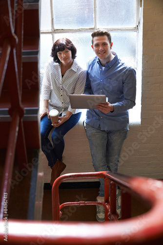 Fotografie, Obraz  Two Businesspeople Having Informal Meeting On Office Stairs