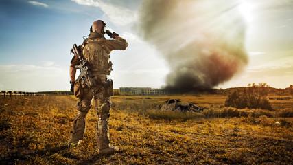 Żołnierz z karabinem patrzy na dym pod miastem. R