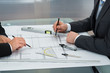 Businessmen Drawing On The Blueprints