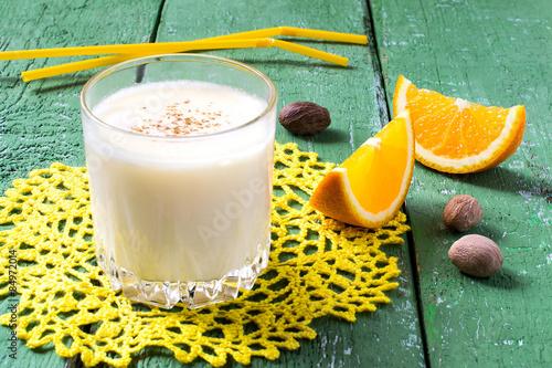 Foto op Aluminium Milkshake The cold milkshake with orange juice, ice cream and nutmeg