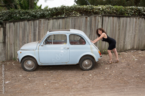 a woman pushing an old broken down car buy this stock photo and