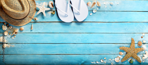 Leinwand Poster seashells on blue wooden plank with straw hat and flip-flop