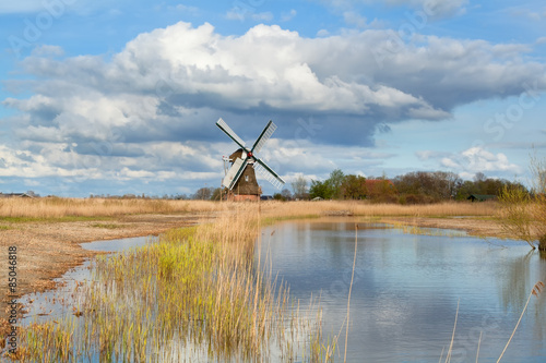 Aluminium Prints Mills Dutch windmill over blue sky by river