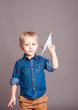 Cute kid boy playing with paper origami plane over gray. Wearing stylish clothes. Childhood.