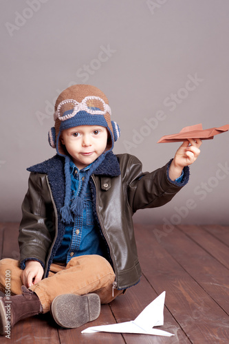 5ed02dd3f31 Cute baby boy wearing stylish leather jacket and aviator cap over gray.  Playing with paper origami planes in room. Sitting on wooden floor. Looking  at .