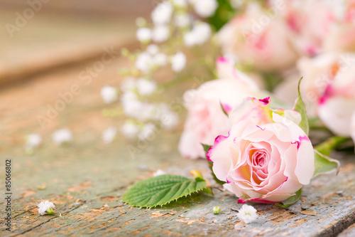 Fotografering  Duftende Rosenblüten auf Holz