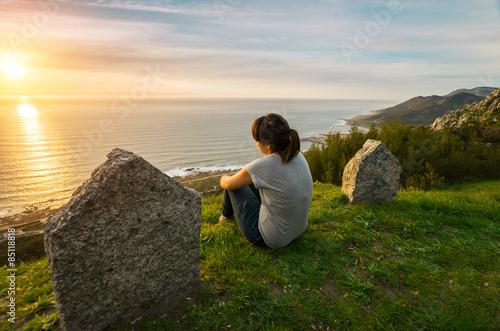 Chica joven observando el atardecer sobre el mar en soledad