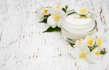 Obraz na płótnie Canvas face and body cream moisturizers with jasmine flowers on white wooden background