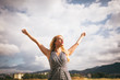 Young blonde woman arms outstretched
