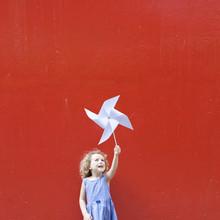 Smiling Girl Holding A Pinwheel In The Air Making A Hong Kong Flag