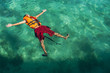 Teenage boy wearing a life jacket, floating in the sea, Salakan Island, Semporna, Sabah, Malaysia