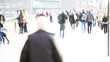 High key, defocused video footage of commuters and shoppers.