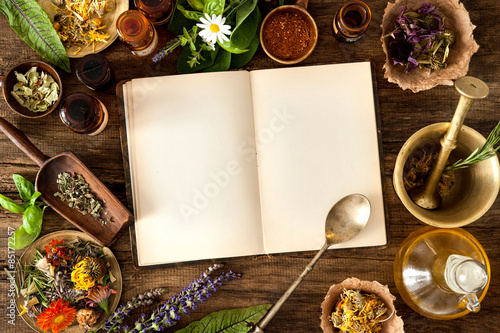 Fotografia  Ancient natural medicine, herbal, vials and recipe book on wooden background