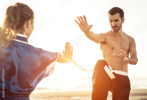 In de dag Vechtsport couple training martial arts on the beach