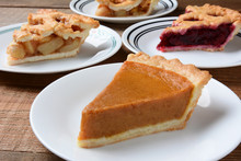 Closeup Of Four Slices Of Pie On Dessert Plates. Focus Is On The Front Slice Of Pumpkin Pie. The Back Plates Have Apple And Cherry Pie.