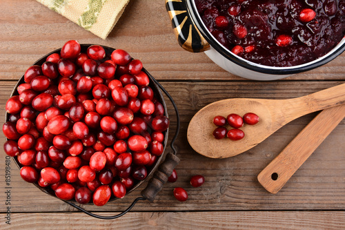 Fotografia  Overhead of a bucket of cranberries and a pot full of whole cranberry sauce on a rustic wooden table