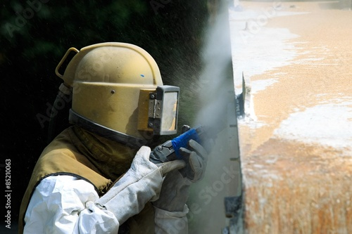 Valokuva  Worker is remove paint by air pressure sand blasting