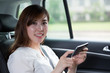 Beautiful asian young woman using mobile phone in car