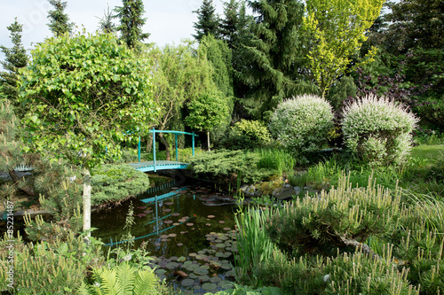 small green footbridge over a pond - 85221487