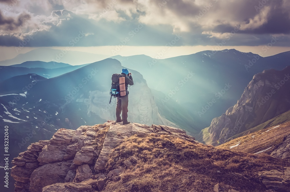 Fototapety, obrazy: Young man standing on a rock and looking at a beautiful mountain