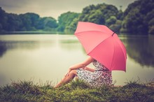 Young Beautiful Woman With Red Umbrella Sitting Near The Pond -
