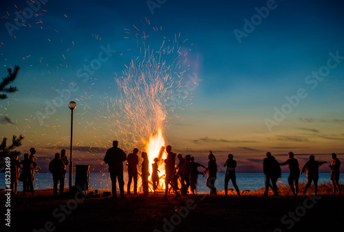 Fototapeta People resting near big bonfire outdoor