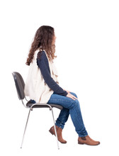 Back View Of Young Beautiful  Woman Sitting On Chair