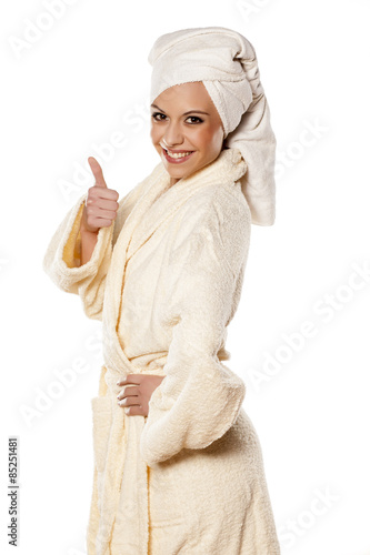 Fotografie, Obraz  smiling woman in bathrobe and towel on her head showing thumbs up
