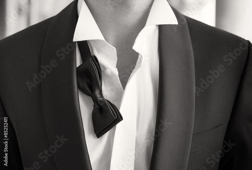 Close-up photo of man in tuxedo with open shirt and loose bow tie Canvas-taulu