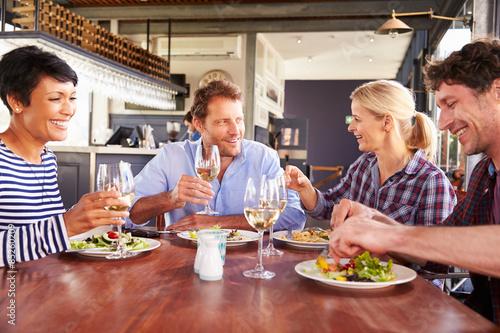Foto op Canvas Kruidenierswinkel A group of friends having lunch in a restaurant