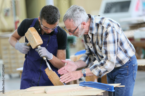 Obraz Young apprentice with teacher working on piece of wood - fototapety do salonu