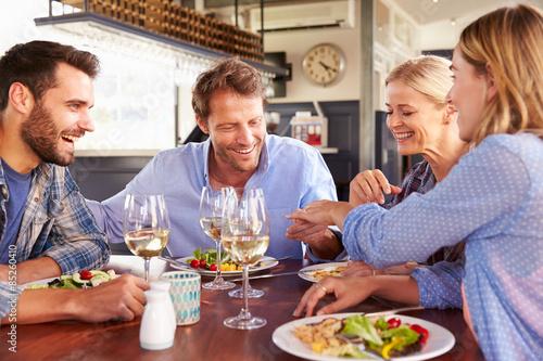 Foto op Canvas Kruidenierswinkel A group of friends eating at a restaurant