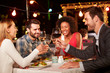 canvas print picture - Four friends eating dinner at rooftop restaurant