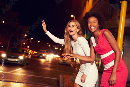 Female friends hailing taxi on city street at night - 85261636
