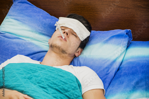 Fotografia  Young man in bed measuring fever with thermometer