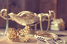 Vintage Golden Bracelet And Silver Vase With Jewelry On Wooden Background