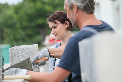 Mason with trainee in construction, building wall Fototapet
