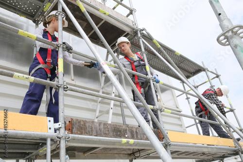 Obraz na plátně Construction workers installing scaffolding on site