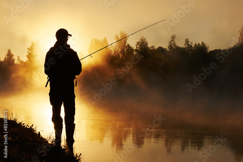 Photo fisher fishing on foggy sunrise