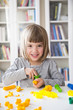 Portrait of smiling little girl playing with yellow modeling clay