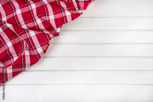 Tuinposter Stof Top view of checkered kitchen towels on wooden table.