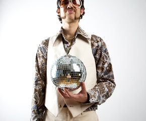 Fototapeta Portrait of a retro man in a 1970s leisure suit and sunglasses holding a disco ball - mirror ball