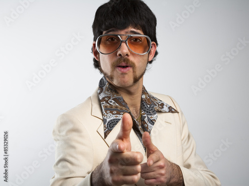Poster  Portrait of a retro man in a 1970s leisure suit and sunglasses pointing to the c