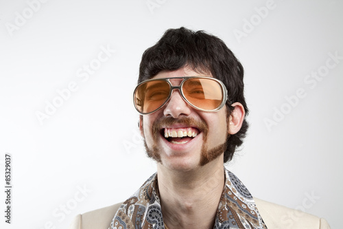 Close up portrait of a retro man in a 1970s leisure suit and sunglasses smiling Wallpaper Mural