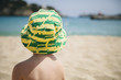 Spain, Mallorca, Porto Christo, back view of little boy sitting on the beach wearing summer hat