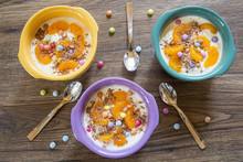 Three Bowls Of Natural Yoghurt With Slices Of Tangerines, Smarties And Chocolate Shaving