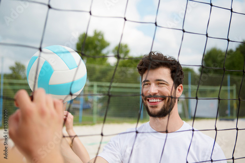 Smiling young man at net of beach volleyball field Poster
